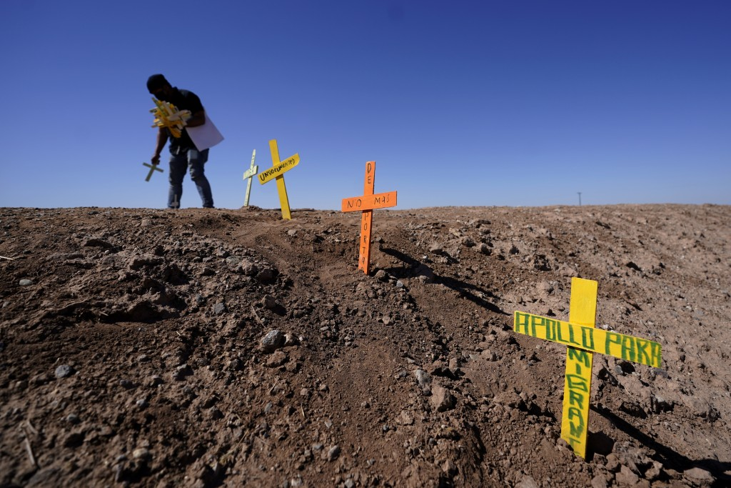 Hugo Castro leaves crosses at the scene of a deadly crash in Holtville, Calif., Tuesday, March 2, 2021. Authorities say a semitruck crashed into an SU...