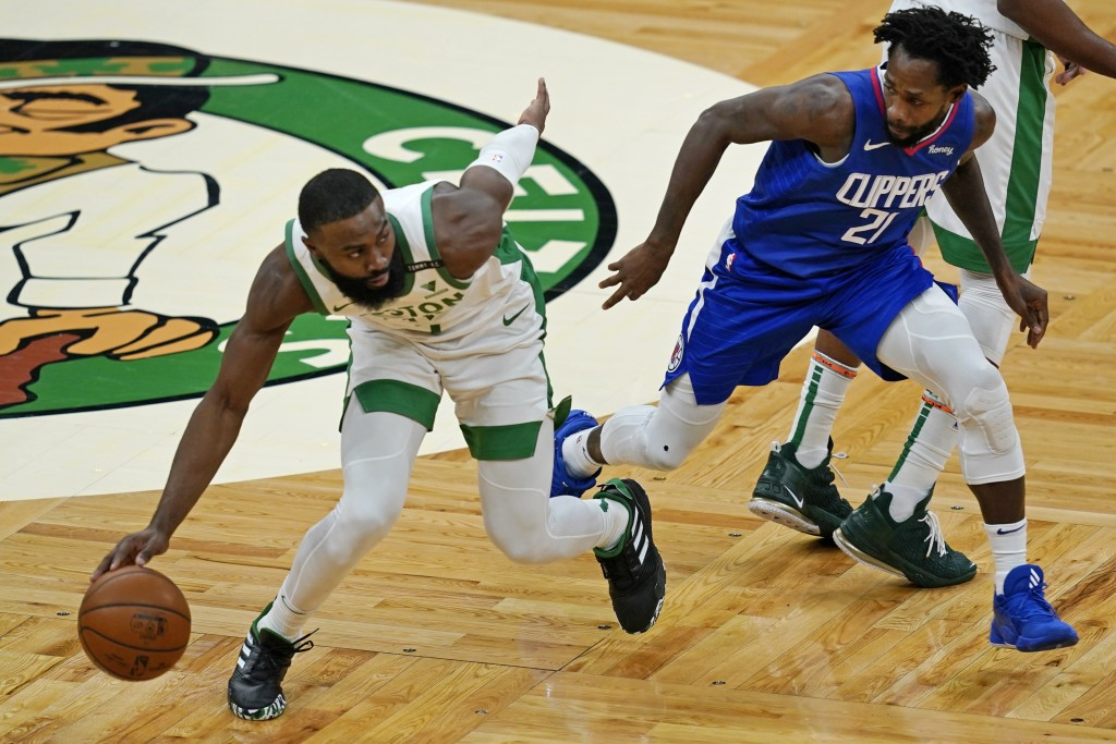 Boston Celtics guard Jaylen Brown, left, dribbles up court under pressure from Los Angeles Clippers guard Patrick Beverley (21) in the third quarter o...