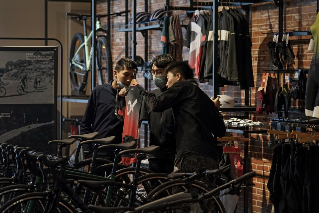 A man wearing a face mask to help curb the spread of the coronavirus checks on a cycling cloth with his friend at a bicycle retail shop selling Americ...