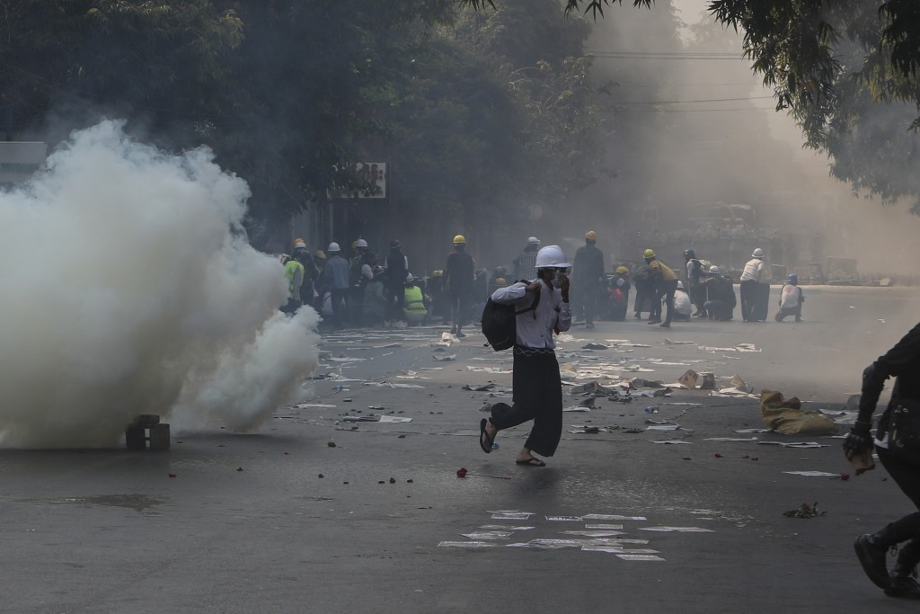 Anti-coup protesters standing behind makeshift-shields brave teargas as others run away in Mandalay, Myanmar, Wednesday, March 3, 2021. Demonstrators ...