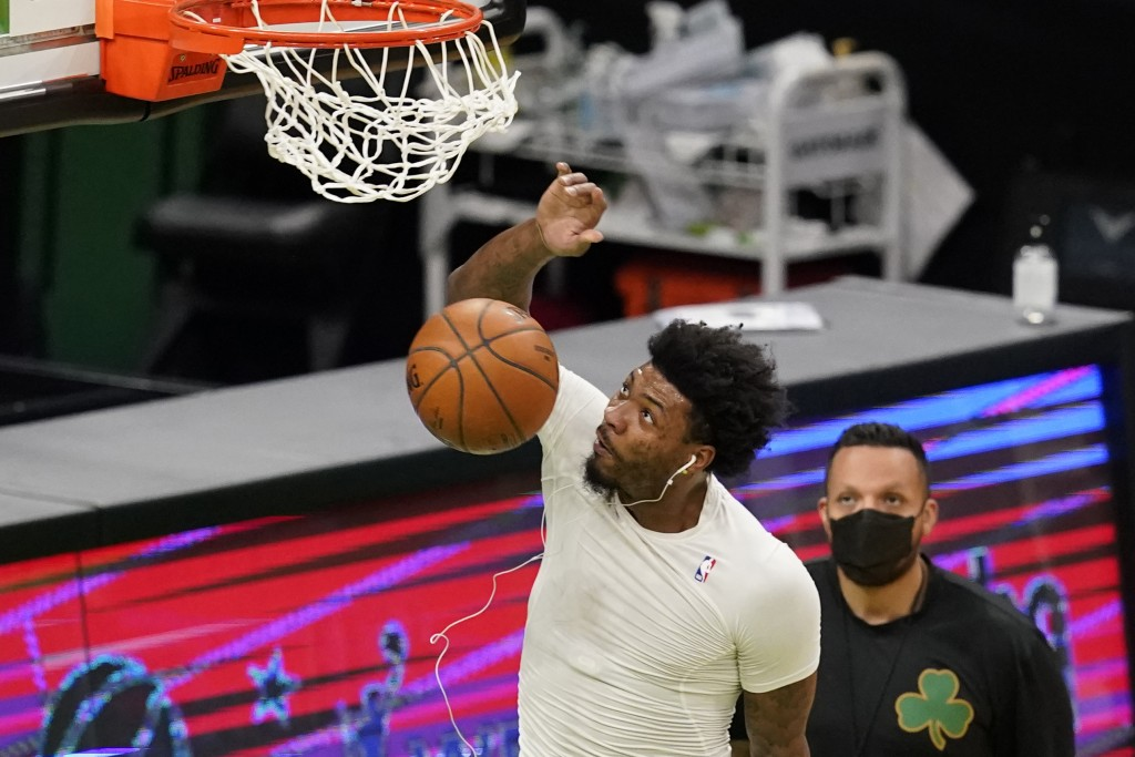 Boston Celtics' Marcus Smart dunks as he warms up before an NBA basketball game against the LA Clippers, Tuesday, March 2, 2021, in Boston. Smart has ...
