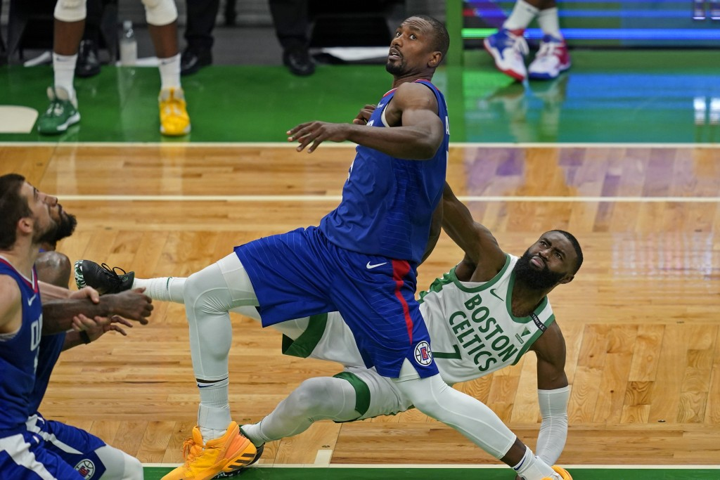 Boston Celtics guard Jaylen Brown (7) falls to the floor after struggling for rebound position with Los Angeles Clippers center Serge Ibaka in the fou...