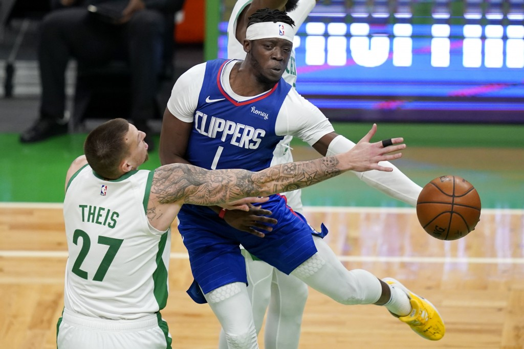 LA Clippers guard Reggie Jackson (1) passes the ball against the defense of Boston Celtics center Daniel Theis (27) in the first quarter of an NBA bas...