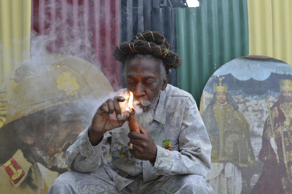 """FILE - In this Aug. 28, 2014 file photo, legalization advocate and reggae legend Bunny Wailer smokes a pipe stuffed with marijuana during a """"reasoning..."""