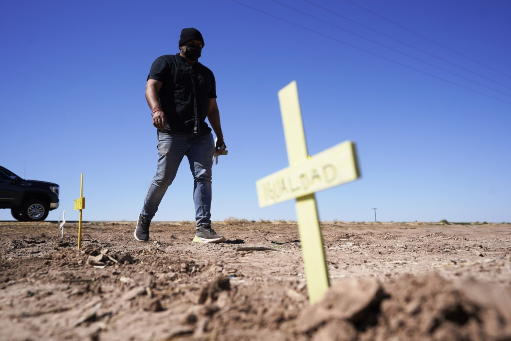 Hugo Castro leaves crosses at the scene of a deadly crash in Holtville, Calif., on Tuesday, March 2, 2021. Authorities say a semi-truck crashed into a...