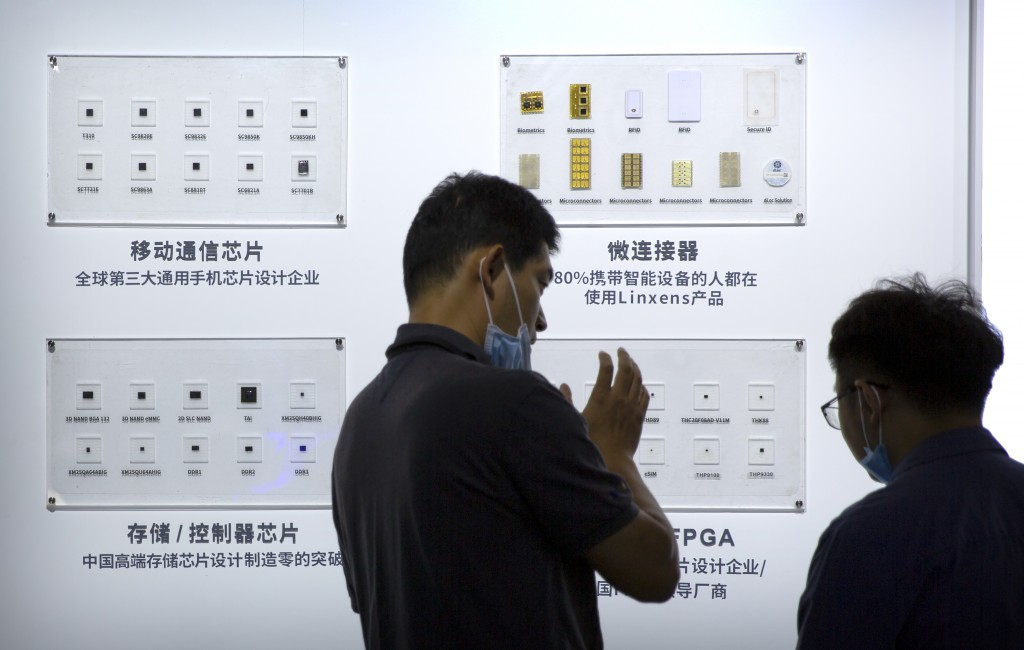 People look at semiconductors on display from the Tsinghua Unigroup at the China Beijing International High Tech Expo in Beijing, Saturday, Sept. 19, ...