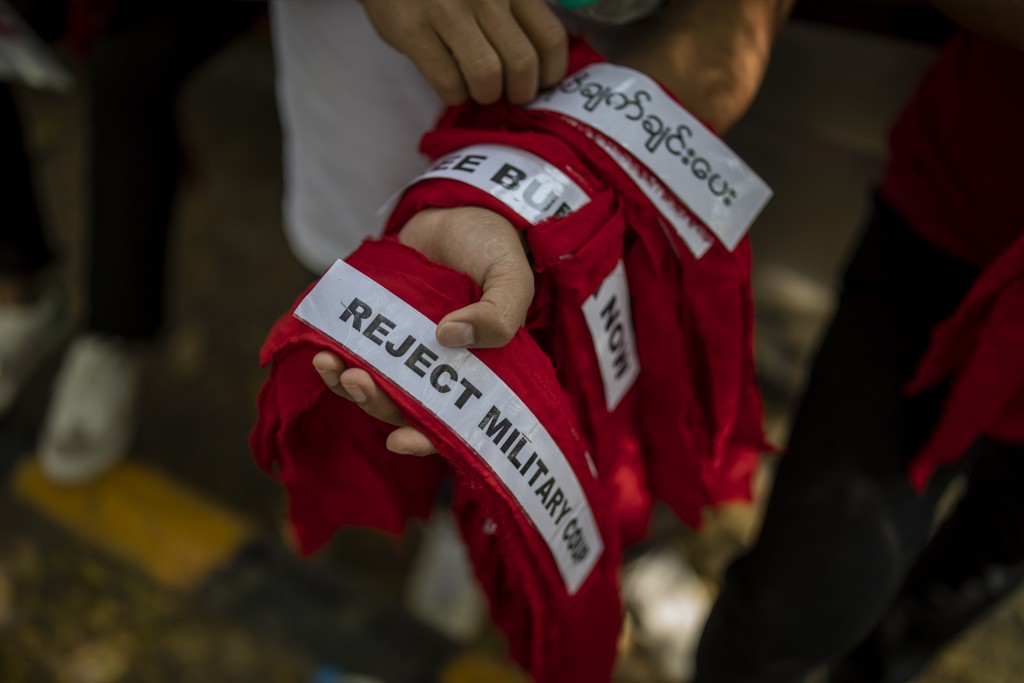 A Chin refugee from Myanmar distributes forehead bands during a protest against military coup in Myanmar, in New Delhi, India, Wednesday, March 3, 202...
