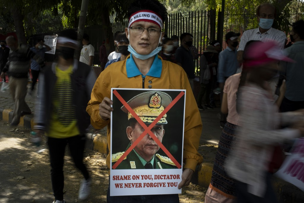 A Chin refugee from Myanmar holds a portrait of Commander in chief, Senior Gen. Min Aung Hlaing during a protest against military coup in Myanmar, in ...