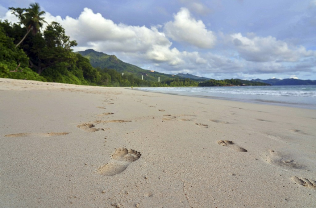 FILE - In this Friday, March 1, 2019 file photo, footprints are seen in the sand on a beach on Mahe island, Seychelles. The president of the Indian Oc...