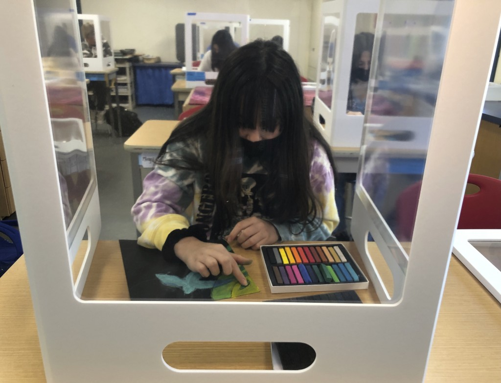 A student works on an art project while surrounded by plexiglass during class at the Sinaloa Middle School in Novato, Calif. on Tuesday, March 2, 2021...