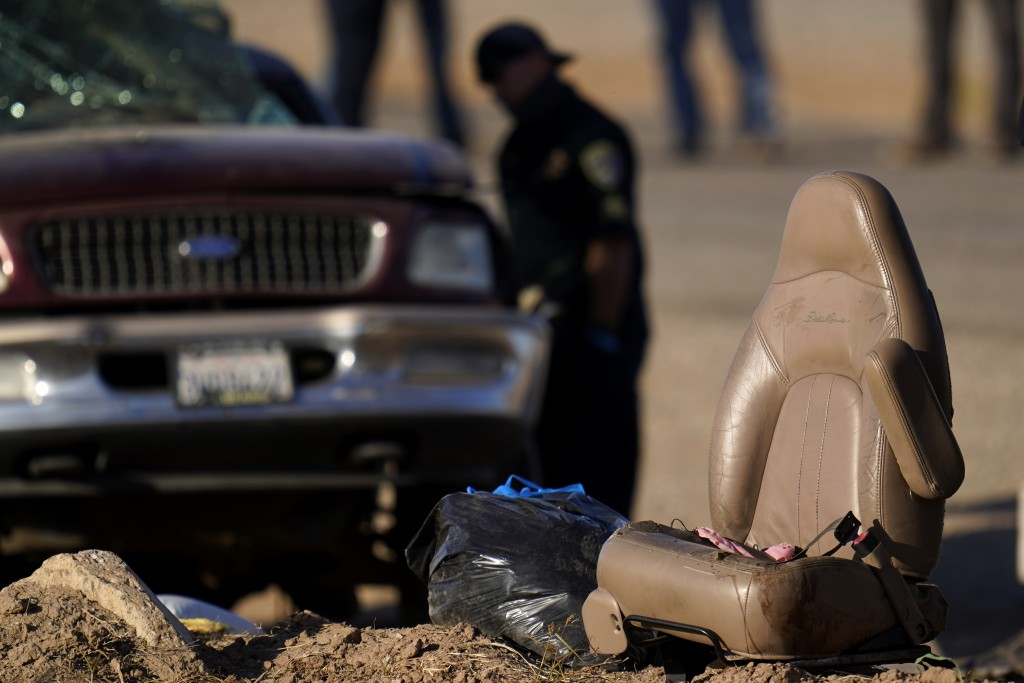 A law enforcement officer examines the scene of a deadly crash in Holtville, Calif., Tuesday, March 2, 2021. Authorities say a semitruck crashed into ...