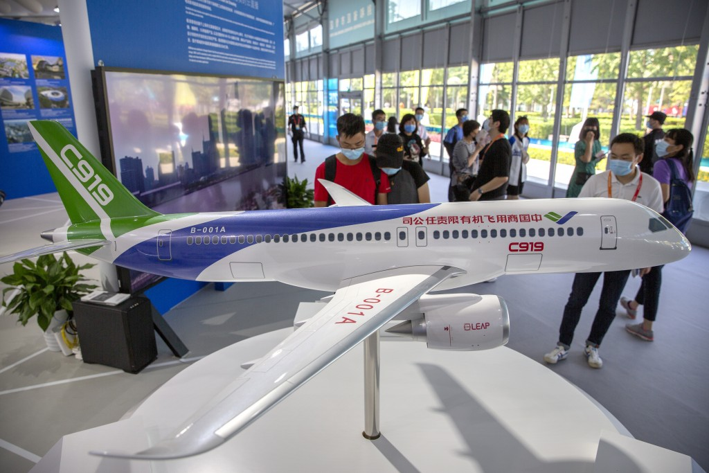 People look at a model of China's domestically-made C919 passenger jet at the China International Fair for Trade in Services (CIFTIS) in Beijing, Satu...