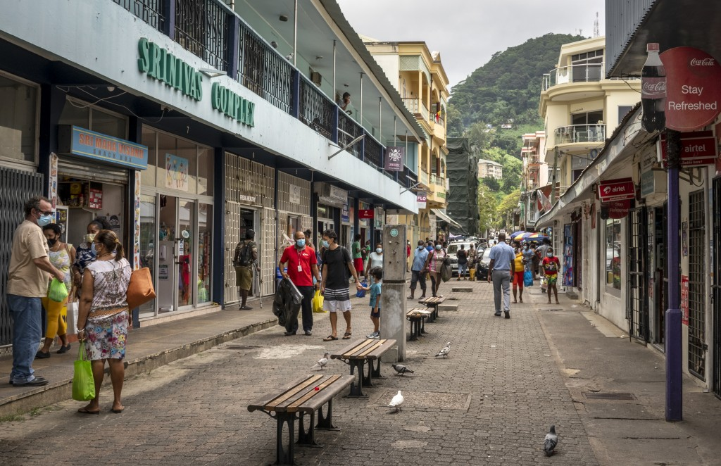 Pedestrians wear masks as they walk on a street in the capital Victoria, Mahe Island, Seychelles Thursday, Feb. 25, 2021. The president of the Indian ...