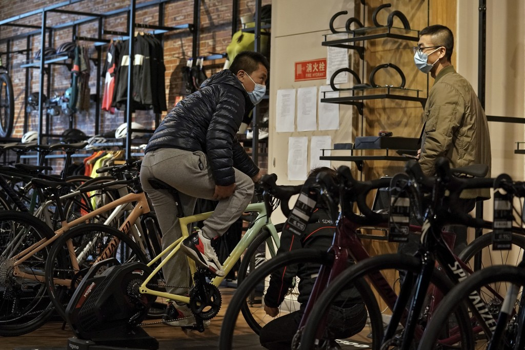 Customers wearing face masks to help curb the spread of the coronavirus chat each other as they try out the American bicycle brand at a retail shop in...