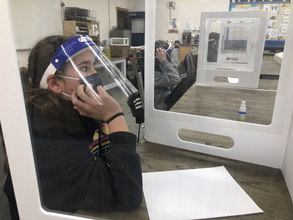 Students wearing face masks and face shields to protect from covid-19 sit at their desks during class at the Sinaloa Middle School in Novato, Calif. o...