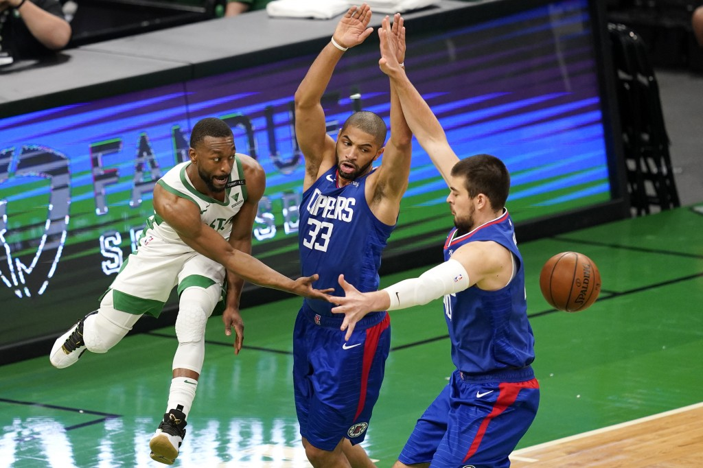 Boston Celtics guard Kemba Walker, left, passes the ball in between LA Clippers forward Nicolas Batum (33) and center Ivica Zubac, right, in the first...