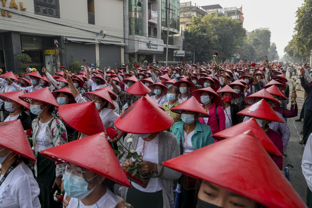 Anti-coup school teachers in their uniform and traditional Myanmar-hats flash three-fingers salute during a demonstration in Mandalay, Myanmar, Wednes...