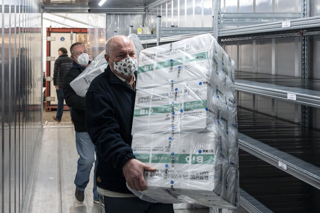 Employees unload the newly arrived coronavirus vaccines from Chinese pharmaceutical company Sinopharm at the logistics base set up to in the parking l...