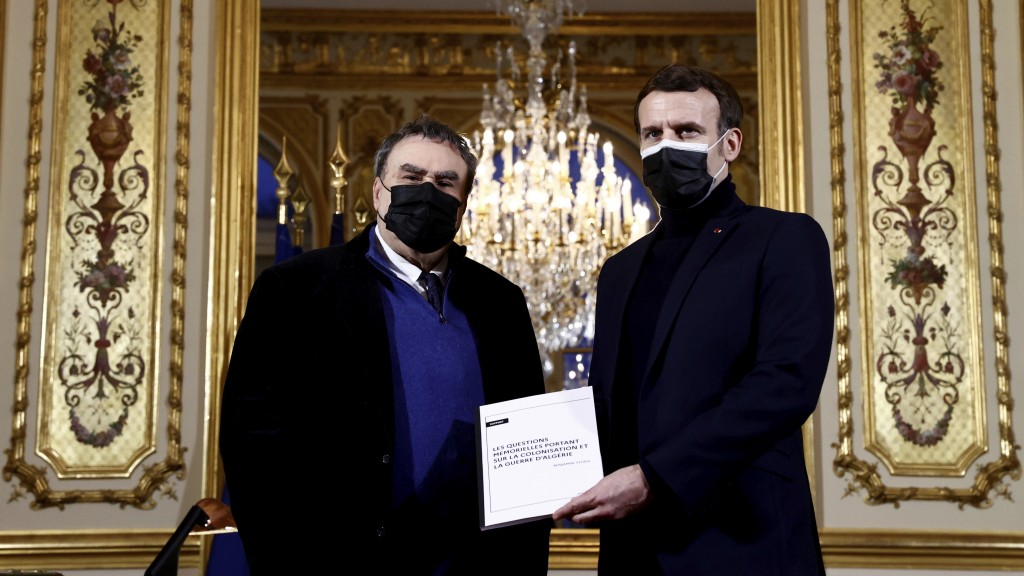 FILE - In this Jan.20, 2021 file photo French President Emmanuel Macron, right, gets a report from French historian Benjamin Stora as he receives the ...