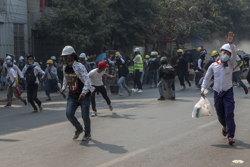 Anti-coup protesters run from teargas and charging riot police and soldiers in Mandalay, Myanmar, Wednesday, March 3, 2021. Demonstrators in Myanmar t...