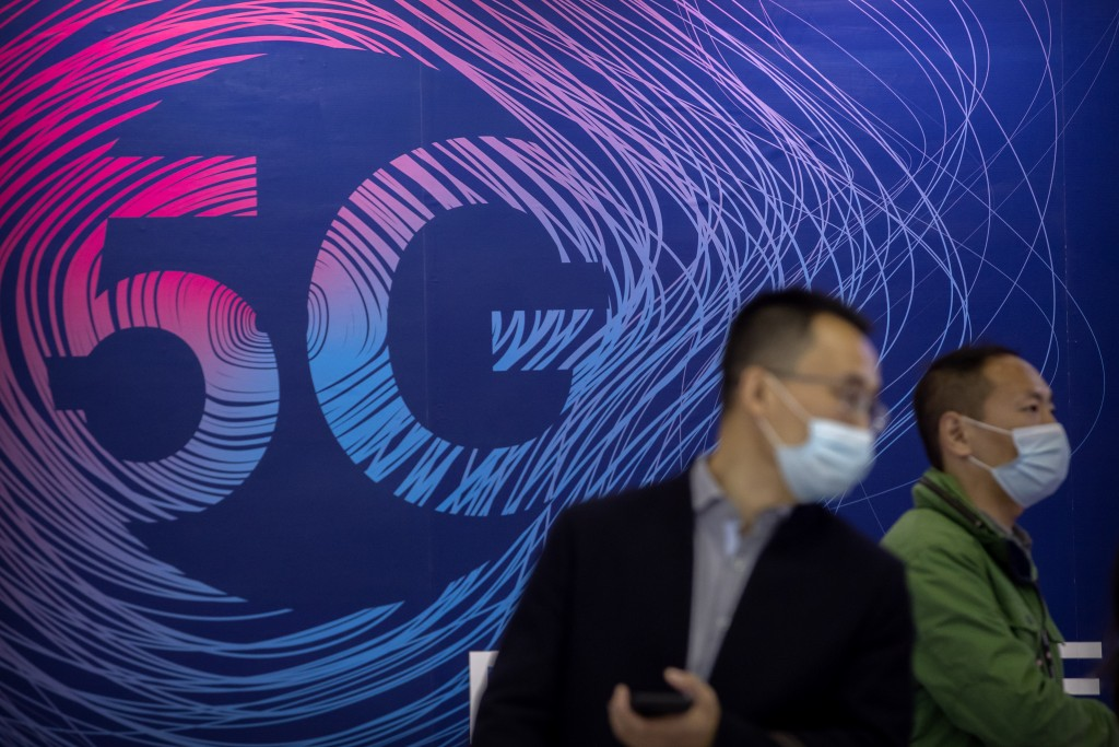 People wearing face masks to protect against the spread of the coronavirus walk past a display advertising 5G wireless services at the PT Expo in Beij...