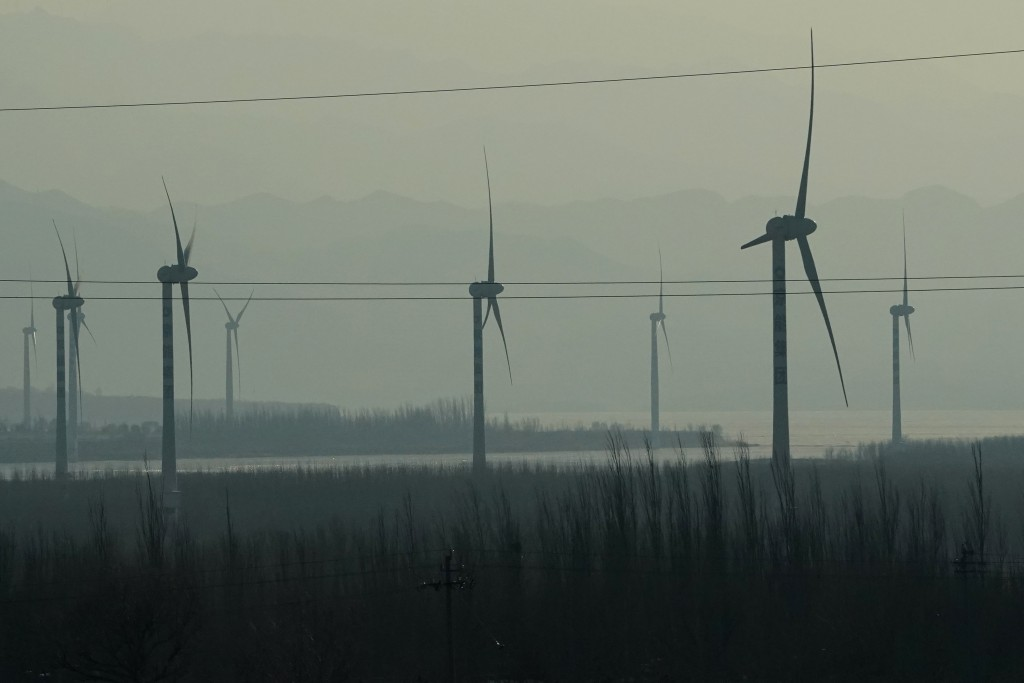 Windmills are seen from a high speed train traveling from Beijing to neighboring Zhangjiakou in northwestern China's Hebei province on Dec. 15, 2020. ...