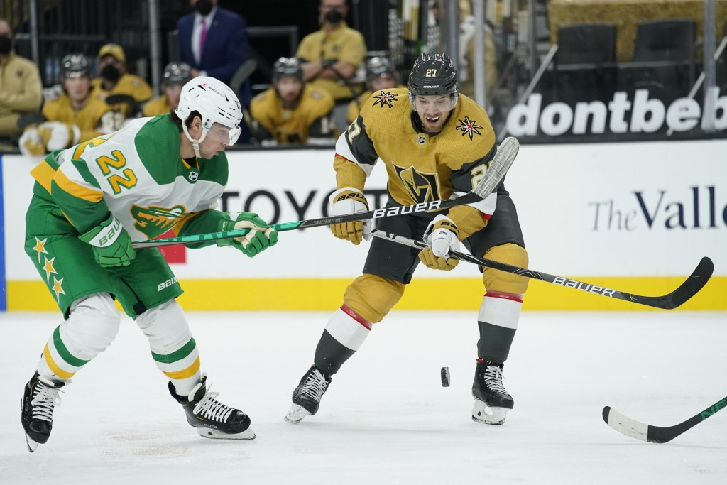 Minnesota Wild left wing Kevin Fiala (22) and Vegas Golden Knights defenseman Shea Theodore (27) vie for the puck during the first period of an NHL ho...