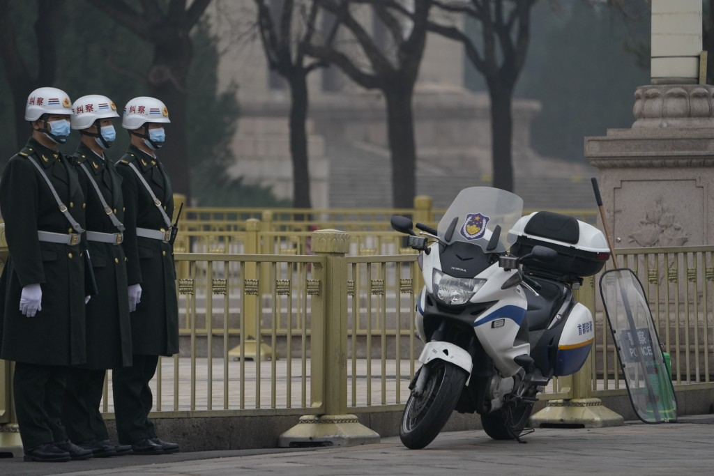 Chinese security personnel stand guard near the Great Hall of the People in Beijing Wednesday, March 3, 2021. In a sign of confidence China has revert...