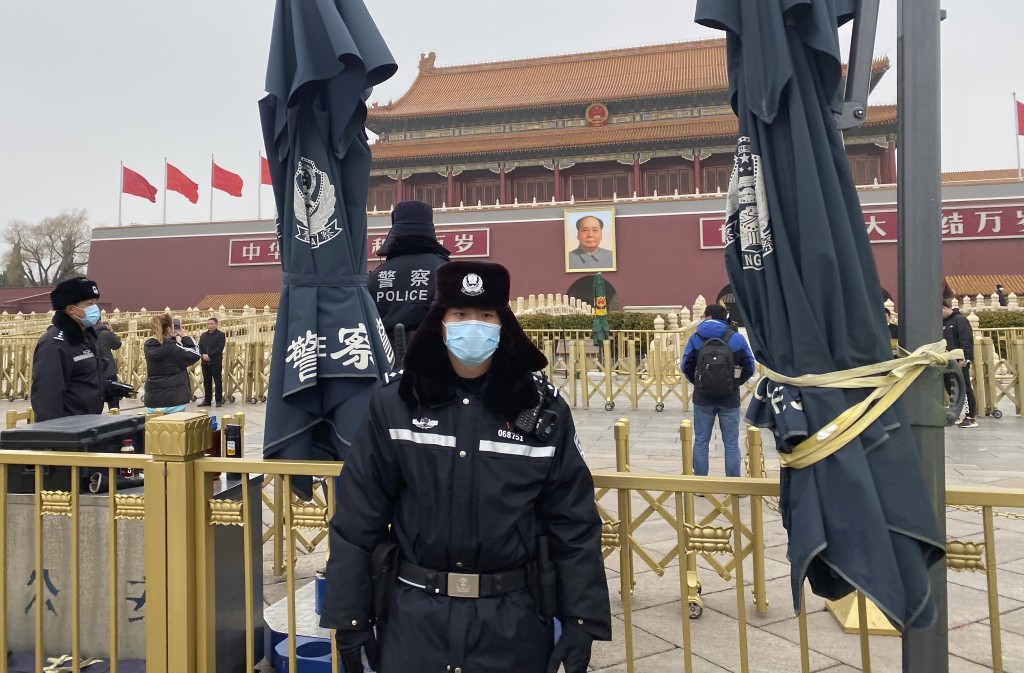 Chinese police officers stand on duty near Tiananmen Gate across from the Great Hall of the People where the annual congress meetings are expected to ...