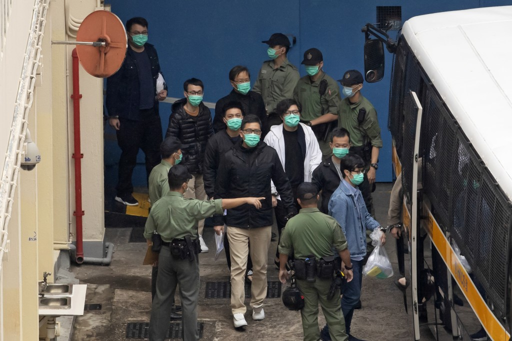 Some of the 47 pro-democracy activists including Lam Cheuk-ting, center, are escorted by Correctional Services officers to a prison van in Hong Kong, ...