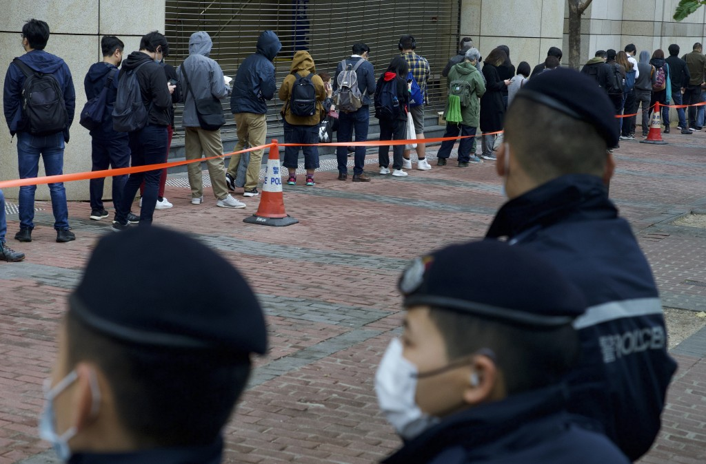 Police officers stand guard as supporters queue up for a hearing outside a court in Hong Kong Thursday, March 4, 2021. A marathon court hearing for 47...