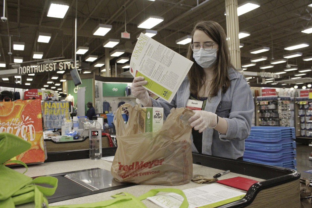 Sara Plush, an employee of the grocery chain Fred Meyer, adds a sheet with information about how to get a COVID-19 vaccine to groceries ordered by a h...
