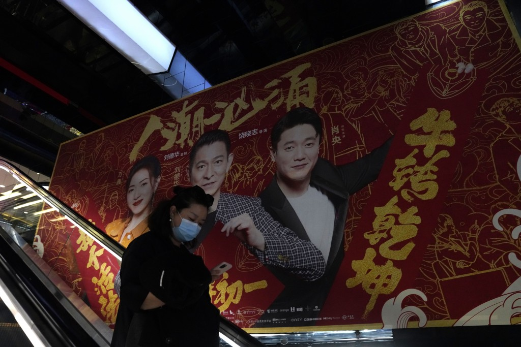 A woman wearing a mask passes by an ad for a movie in Beijing Thursday, Feb. 25, 2021. The state of the world's second largest economy takes precedenc...