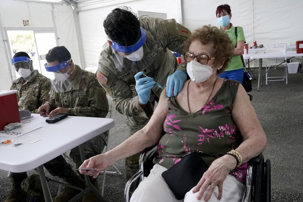 FILE - In this March 3, 2021, file photo, In this Loida Mendez, 86, gets the first dose of the Pfizer COVID-19 vaccine from U.S. Army medic Luis Perez...