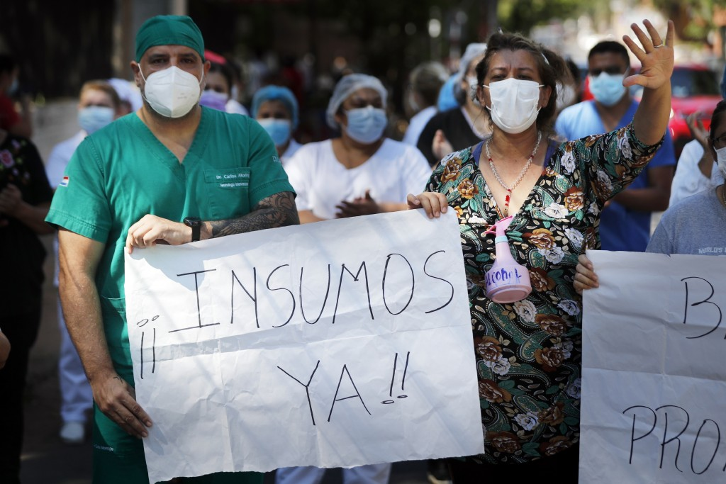"Protestors hold sign in Spanish that reads ""Supplies now!"" as they demand more materials for hospital in Asuncion, Paraguay."