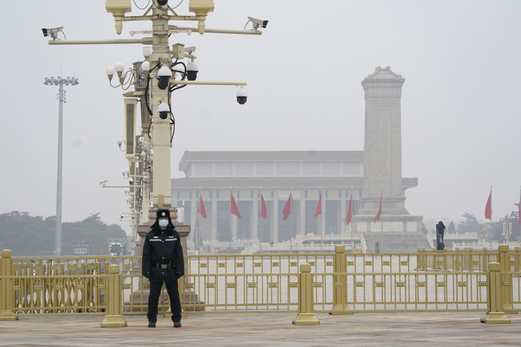 A Chinese police officer guards an empty Tiananmen Square near the Great Hall of the People in Beijing on Wednesday, March 3, 2021. In a sign of confi...