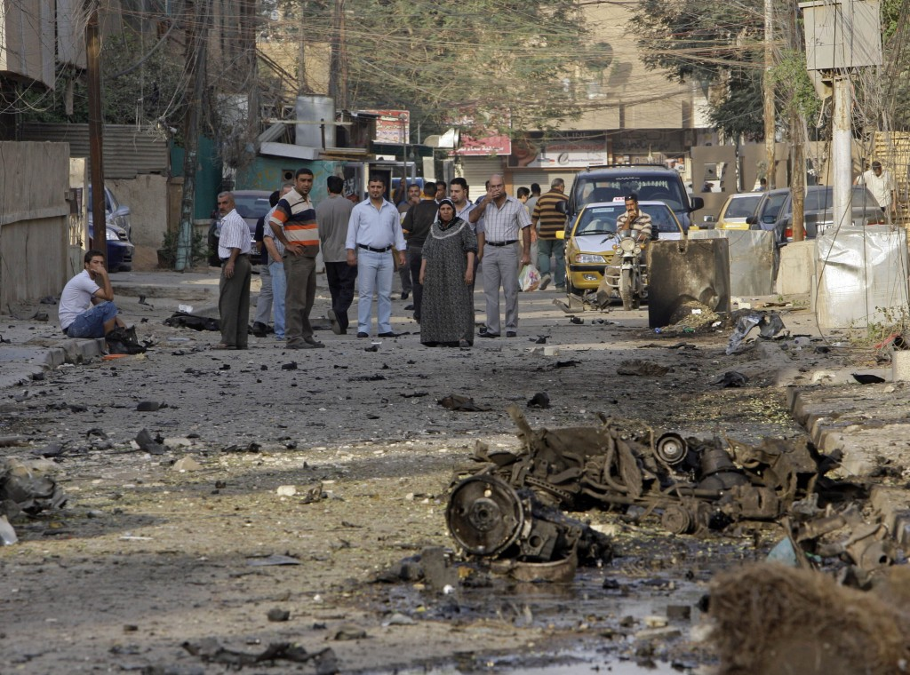 File - In this Monday Nov. 1, 2010 file photo, Iraqis inspect the scene of a car bomb attack in front of a Our Lady of Salvation Church in Baghdad, in...