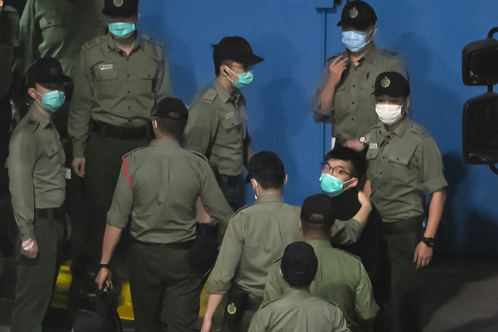 FILE - In this Tuesday, March 2, 2021, file photo, Joshua Wong, right, one of the 47 pro-democracy Hong Kong activists, is escorted by Correctional Se...