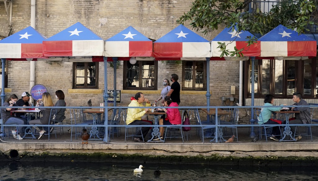 Diners eat at a restaurant on the River Walk, Wednesday, March 3, 2021, in San Antonio. Gov. Greg Abbott says Texas is lifting a mask mandate and lift...