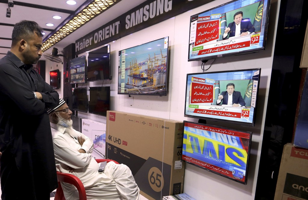 People watch a live address to the nation by Pakistan's Prime Minister Imran Khan, at a shop in Karachi, Pakistan, Thursday, March 4, 2021. Khan on Th...