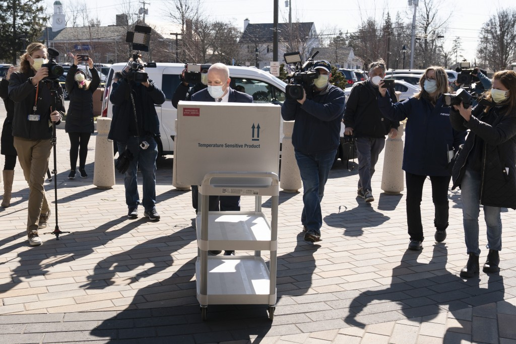 Pharmacist Jack Kann, center, delivers a case of the Johnson & Johnson COVID-19 vaccine at South Shore University Hospital, Wednesday, March 3, 2021, ...