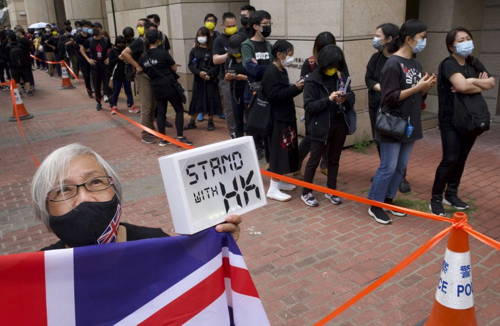 FILE - In this Monday, March 1, 2021, file photo, a woman holds a placard and a U.K. flag, as supporters queue up outside a court to try to get in for...