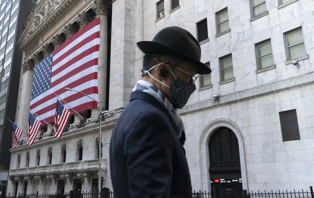FILE - In this Nov. 16, 2020 file photo a man wearing a mask passes the New York Stock Exchange in New York. Stocks are moving modestly higher in earl...
