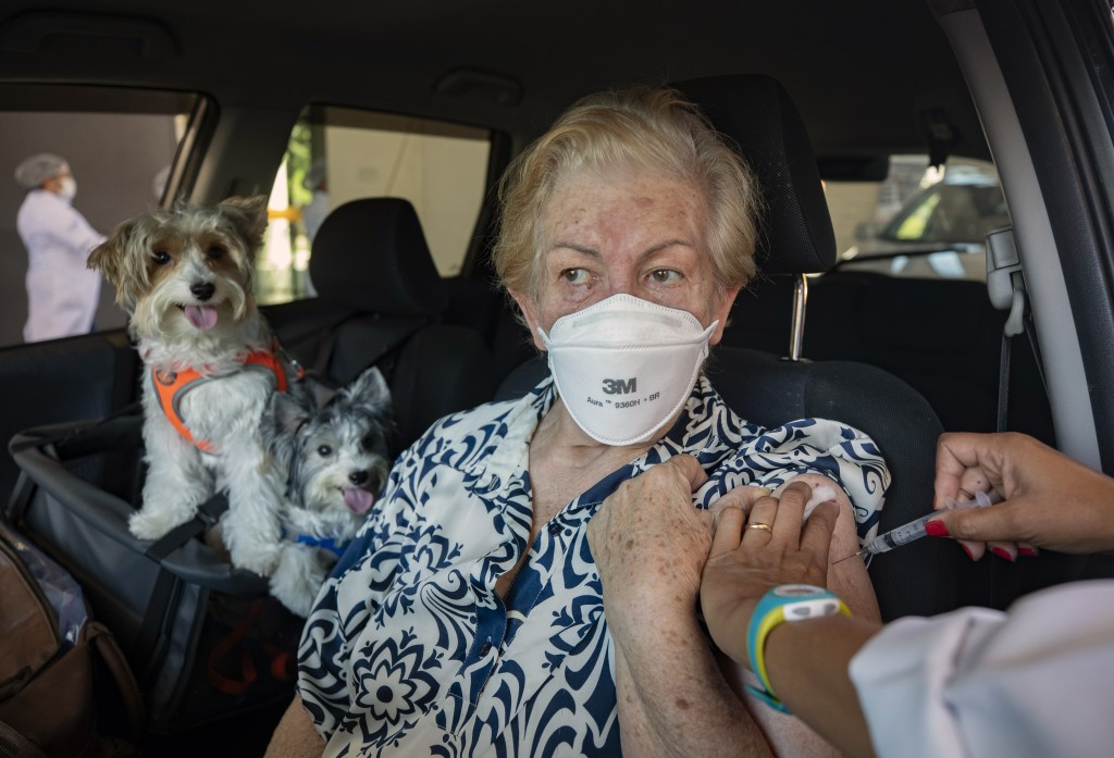 Maria Helena Alcantara gets a shot of the Sinovac COVID-19 vaccine while she sits in her car with her pets during a priority vaccination program for s...