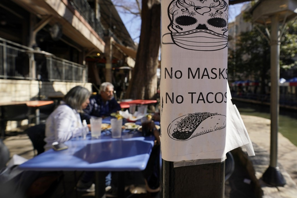 A sign requiring make is seen near diners eating at a restaurant on the River Walk, Wednesday, March 3, 2021, in San Antonio. Gov. Greg Abbott says Te...