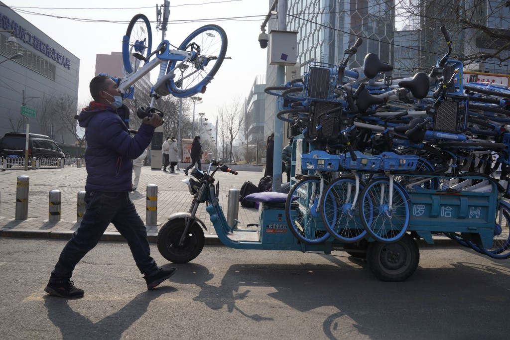A worker collects bicycles from a bike-sharing service in Beijing Thursday, Feb. 25, 2021. The state of the world's second largest economy takes prece...