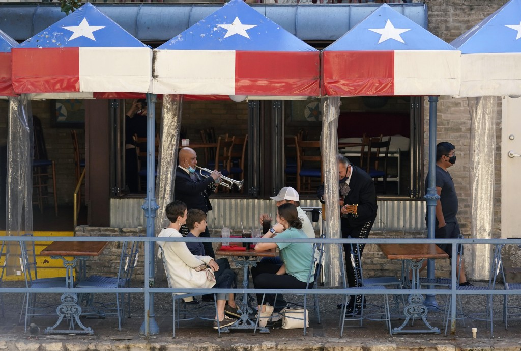 Mariachi perform for diners at a restaurant on the River Walk, Wednesday, March 3, 2021, in San Antonio. Gov. Greg Abbott says Texas is lifting a mask...