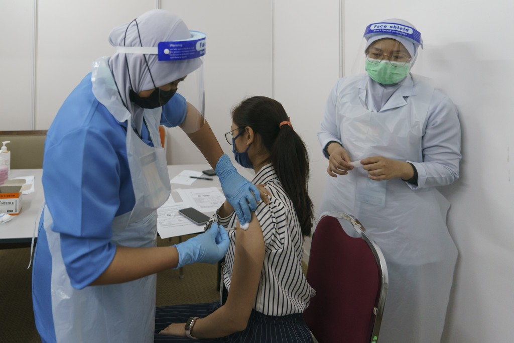 A health worker administers the Pfizer COVID-19 vaccine to a staff member at a vaccination center in Serdang, outskirt of Kuala Lumpur, Malaysia, Thur...