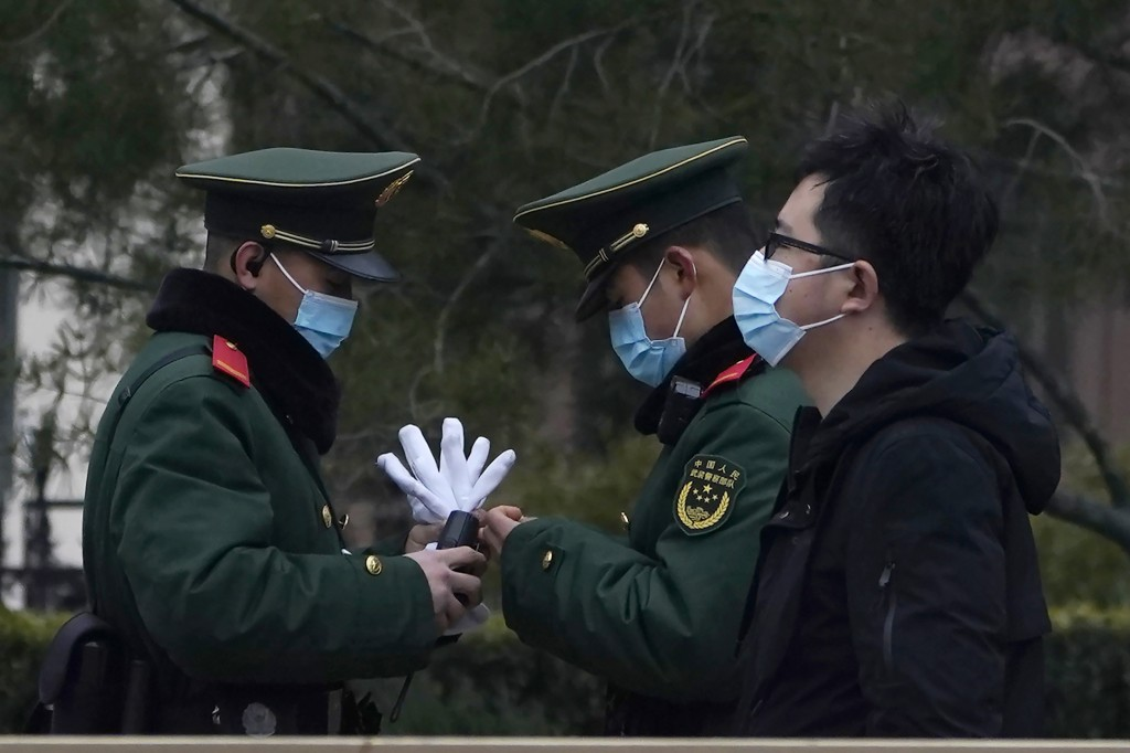 Chinese paramilitary policemen change shifts on the streets of Beijing near the Great Hall of the People Wednesday, March 3, 2021. In a sign of confid...