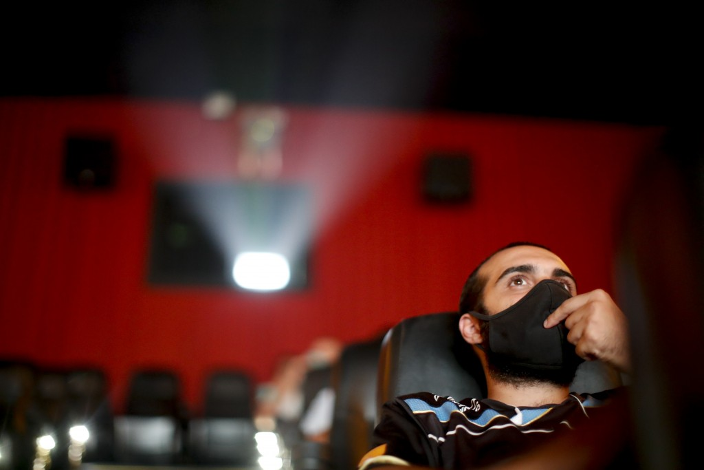 A man watches a movie at a cinema after almost a year of theaters being closed due to the COVID-19 pandemic, in Buenos Aires, Argentina, Wednesday, Ma...